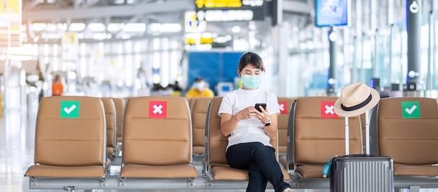 Jonge vrouw die gezichtsmasker draagt en mobiele smartphone gebruikt in luchthaven, bescherming coronavirus-infectie (covid-19), aziatische vrouwenreiziger zittend op een stoel.