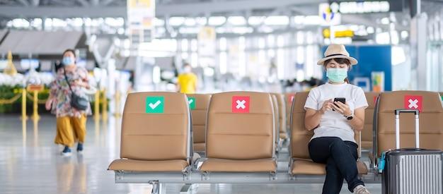 Jonge vrouw die gezichtsmasker draagt en mobiele smartphone gebruikt in luchthaven