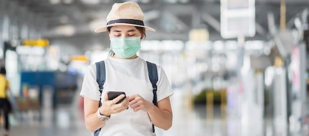 Jonge vrouw die gezichtsmasker draagt en mobiele smartphone gebruikt in luchthaventerminal