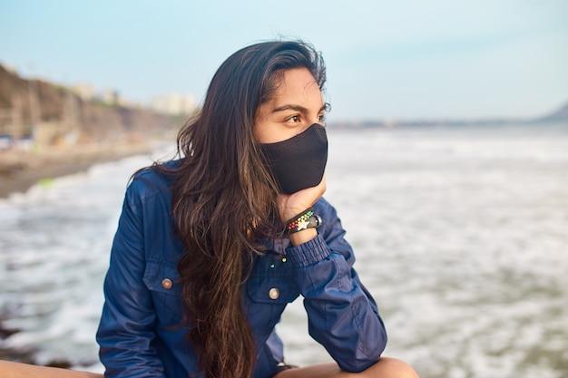 Jonge vrouw die gezichtsmasker draagt op de pier. buitensport bij zonsondergang. vrije vrouw die bij zonsondergang rust