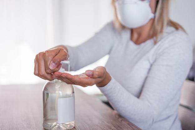 Jonge vrouw die gezichtsmasker draagt terwijl ze haar handen reinigt met ontsmettingsgel voor preventie van coronavirus - hygiëne stopt met het verspreiden van covid 19-concept
