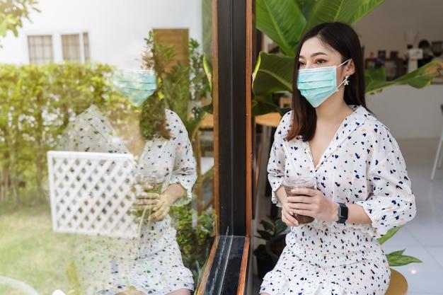 Jonge vrouw die gezichtsmasker draagt voor bescherming coronavirus (covid-19) en chocolademelk drinkt in café