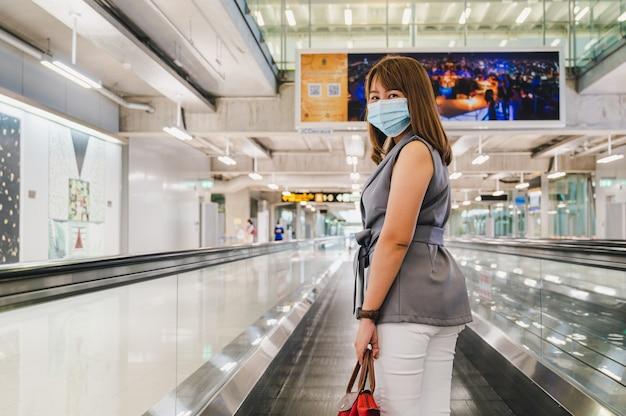 Jonge vrouw die gezichtsmasker in luchthaven van thailand draagt