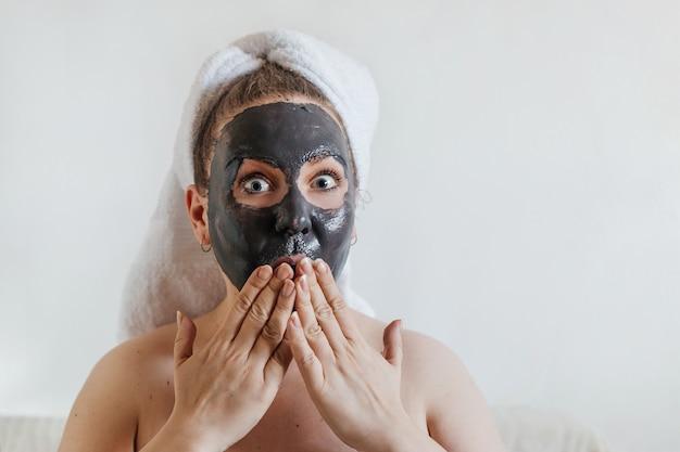Jonge vrouw die gezichtsmasker van zwarte modderklei op haar gezicht toepast