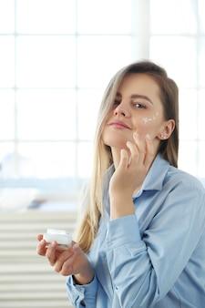 Jonge vrouw die gezichtsroom uitspreiden. huidverzorging concept.