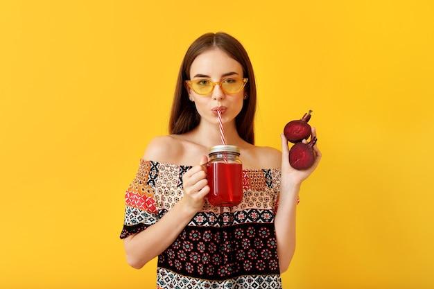 Jonge vrouw die gezond bietensap drinkt op kleur