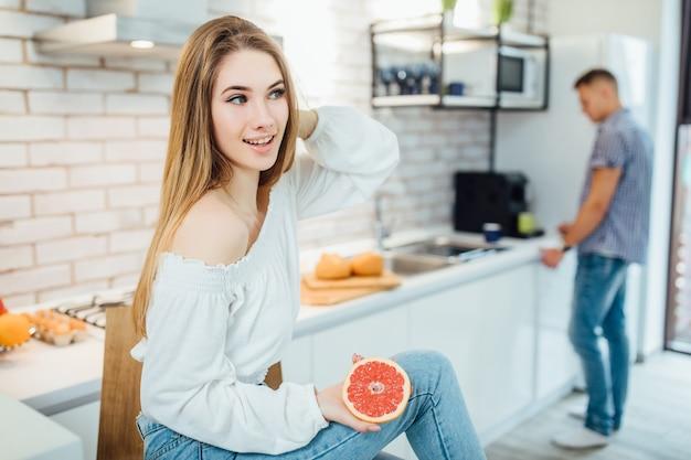 Jonge vrouw die gezond ontbijt grapefruit eet.