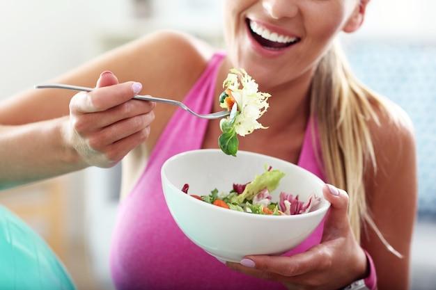 Jonge vrouw die gezonde salade eet na training