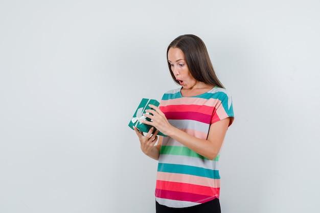 Jonge vrouw die giftdoos in t-shirt, broek onderzoekt en verbaasd, vooraanzicht kijkt.