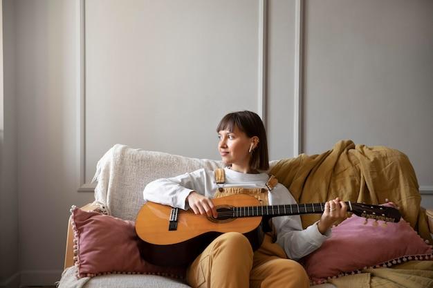 Jonge vrouw die gitaar speelt binnenshuis met kopieerruimte