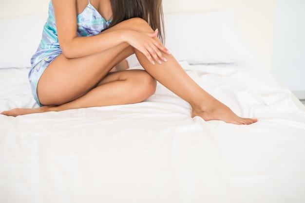 Jonge vrouw die gladde zijdezachte huidbenen tonen na epileren op bed thuis