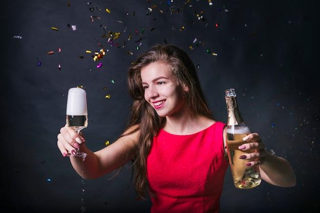 Jonge vrouw die glas champagne bekijkt