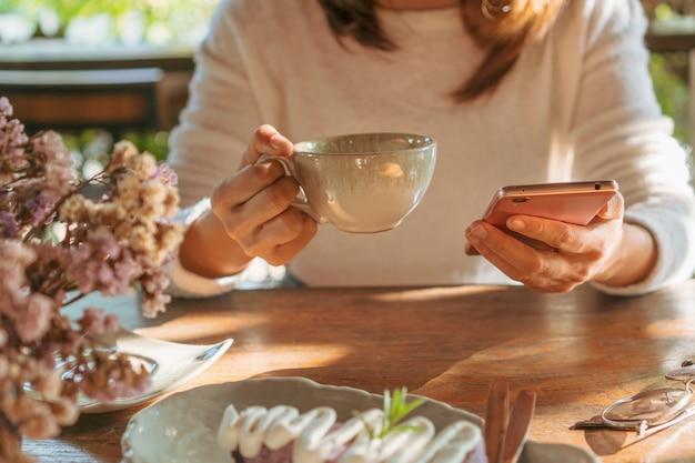 Jonge vrouw die goed nieuws op mobiele telefoon leest tijdens rust in koffiewinkel, gelukkig aziatisch wijfje die op haar foto op slimme telefoon letten terwijl het drinken van koffie in koffie in vrije tijd.