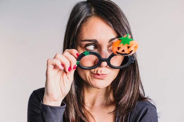 Jonge vrouw die grappige halloween-glazen en het glimlachen draagt. levensstijl binnenshuis. skelet kostuum