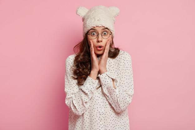 Jonge vrouw die grappige hoed en overhemd draagt