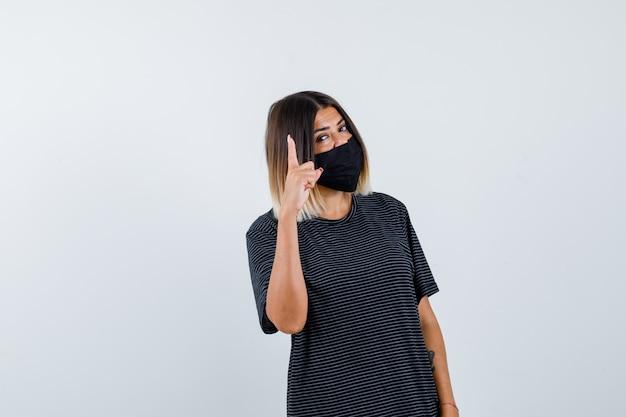 Jonge vrouw die greep op een minuutgebaar in zwarte kleding, zwart masker toont en ernstig kijkt. vooraanzicht.