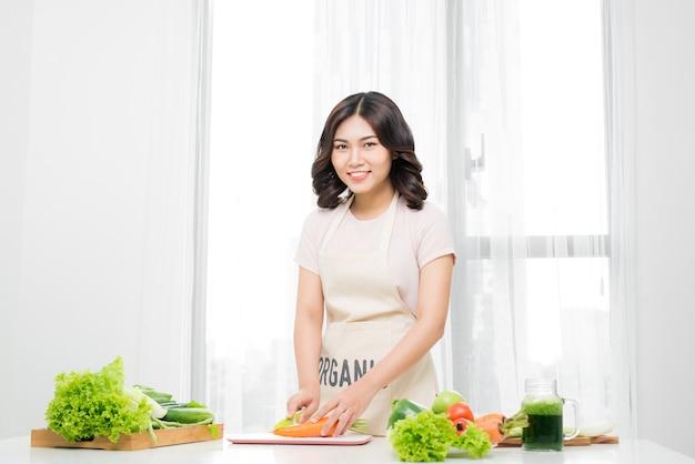 Jonge vrouw die groenten in keuken thuis snijdt
