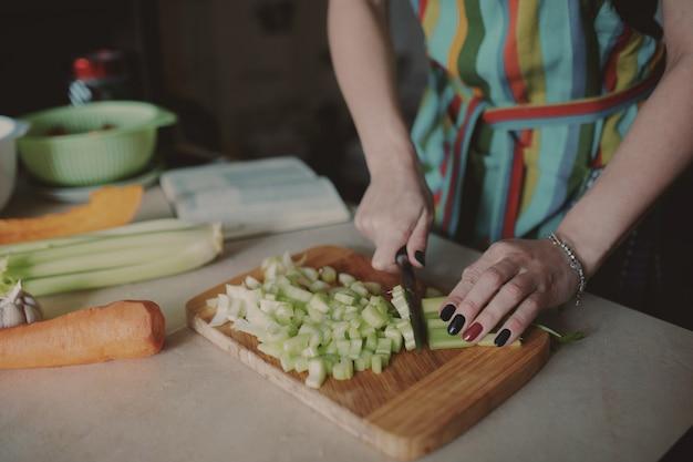 Jonge vrouw die groenten snijdt