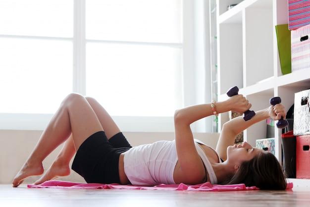 Jonge vrouw die gymnastiek- oefeningen doet