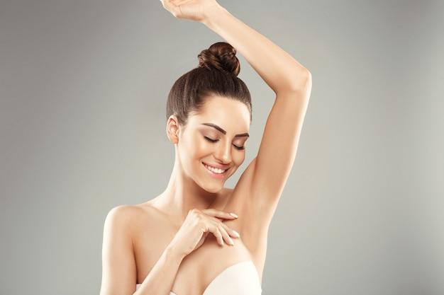 Jonge vrouw die haar armen omhoog houdt en schone oksels toont