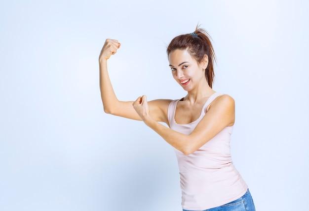 Jonge vrouw die haar armspieren demonstreert, profielweergave
