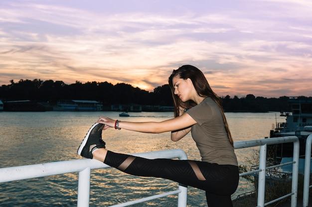 Jonge vrouw die haar been uitrekt dichtbij rivier bij zonsondergang