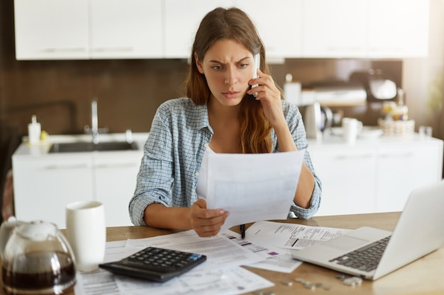 Jonge vrouw die haar begroting controleert en belastingen doet
