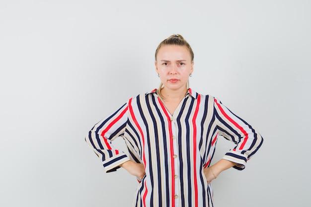Jonge vrouw die haar beide handen op de heupen in gestreepte blouse zet en twijfelachtig kijkt