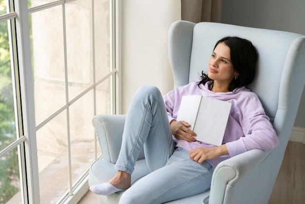 Jonge vrouw die haar boek vasthoudt terwijl ze uit het raam kijkt