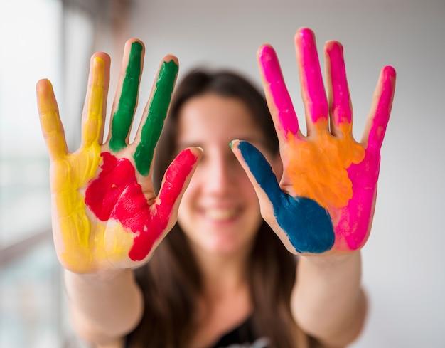 Jonge vrouw die haar geschilderde handen toont