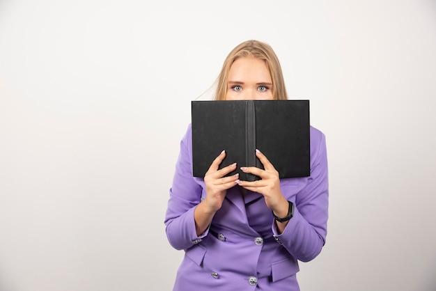 Jonge vrouw die haar gezicht bedekt met geopende tablet op wit.