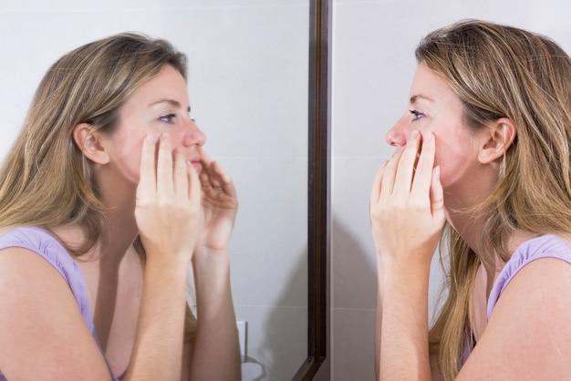 Jonge vrouw die haar gezicht in de spiegel controleert