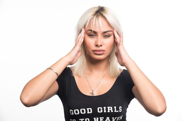 Jonge vrouw die haar gezicht op witte muur drukt.