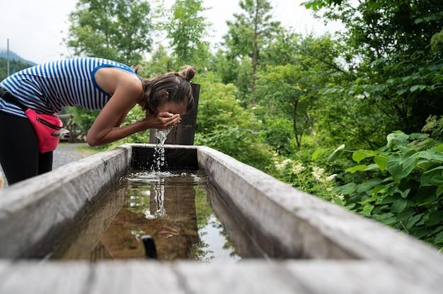 Jonge vrouw die haar gezicht wast in een houten trog die in de groene natuur is geplaatst.