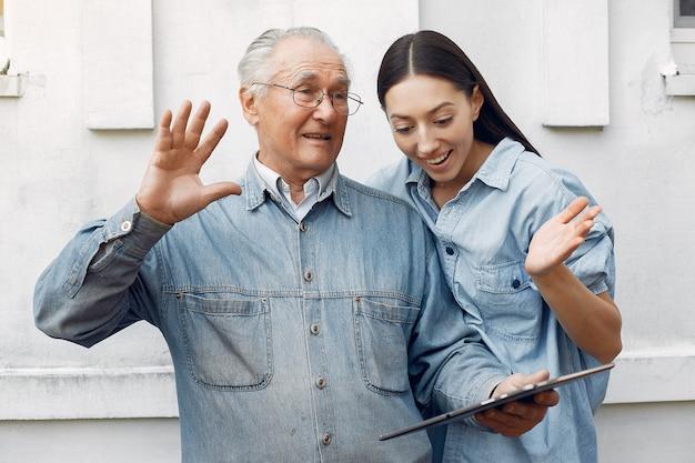 Jonge vrouw die haar grootvader onderwijst hoe te om een tablet te gebruiken