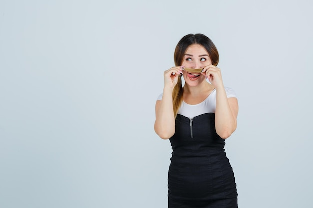 Jonge vrouw die haar haar als snor houdt en tong uitsteekt