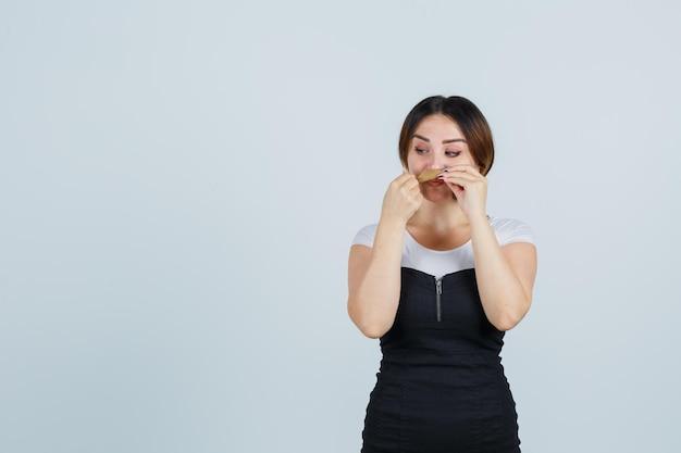 Jonge vrouw die haar haar als snor vasthoudt