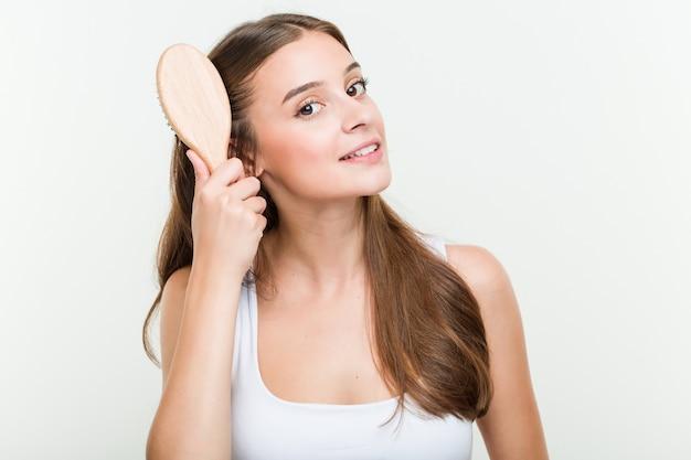 Jonge vrouw die haar haar borstelt