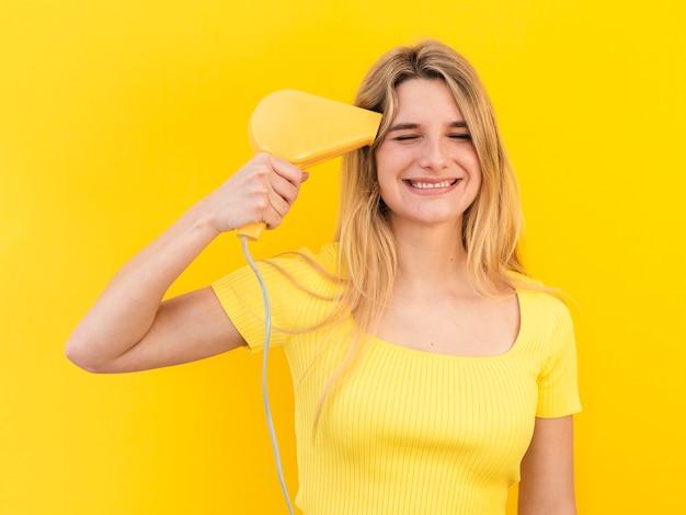 Jonge vrouw die haar haar droogt