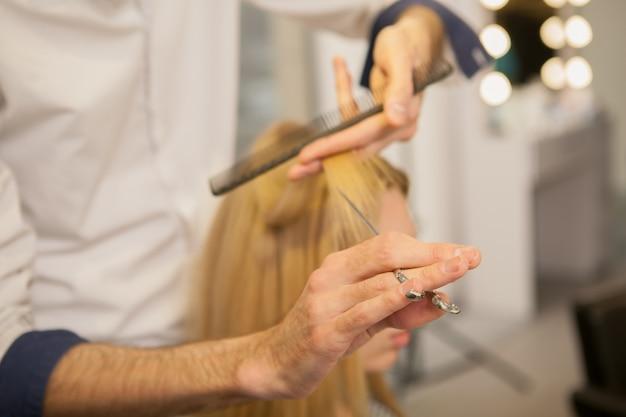 Jonge vrouw die haar haar heeft dat door kapper wordt gestileerd