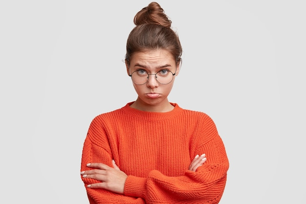 Jonge vrouw die haar haar in een broodje en een grote sweater draagt