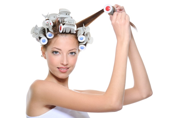 Jonge vrouw die haar haar krult aan de haarkrulspelden - die op wit worden geïsoleerd