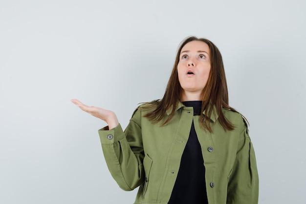 Jonge vrouw die haar hand met open palm in groen jasje opheft en verbaasd kijkt. vooraanzicht.