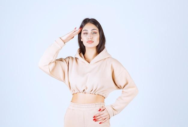 Jonge vrouw die haar hand naar voren brengt en vooruit kijkt of groet in een militaire stijl