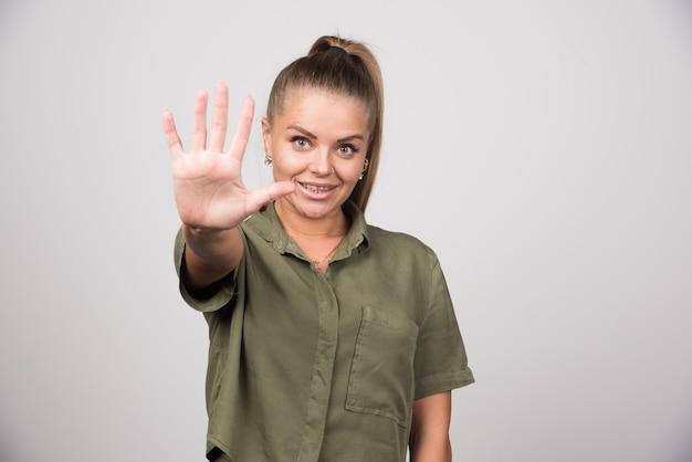 Jonge vrouw die haar hand op grijze muur toont.