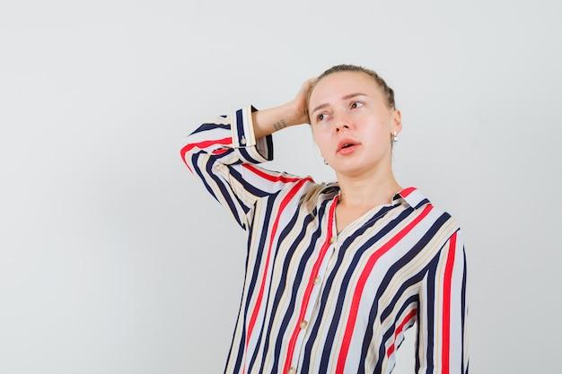 Jonge vrouw die haar hand op het hoofd legt en over iets in gestreepte blouse denkt en verward kijkt