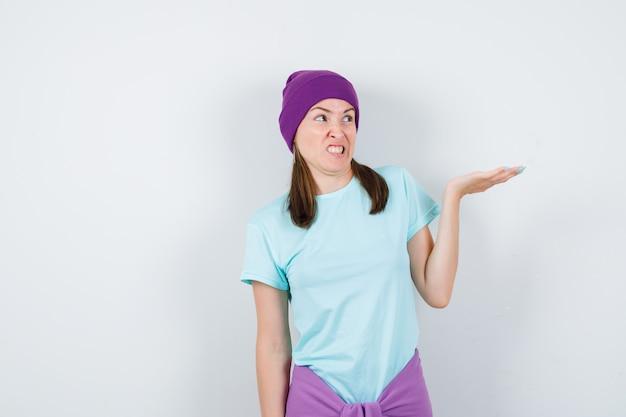 Jonge vrouw die haar hand uitrekt, ernaar kijkt met een grimas in blauw t-shirt, paarse muts en er gehaast uitziet, vooraanzicht.