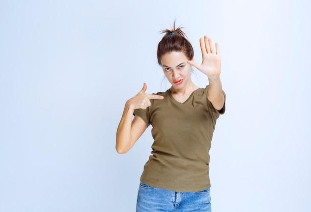 Jonge vrouw die haar handen gebruikt, voorkomt en stopt iets