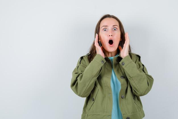 Jonge vrouw die haar handen in de buurt van het gezicht in een groen jasje houdt en er geschokt uitziet. vooraanzicht.