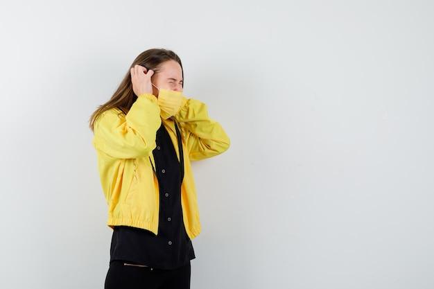 Jonge vrouw die haar handen op de oren drukt en er geïrriteerd uitziet?